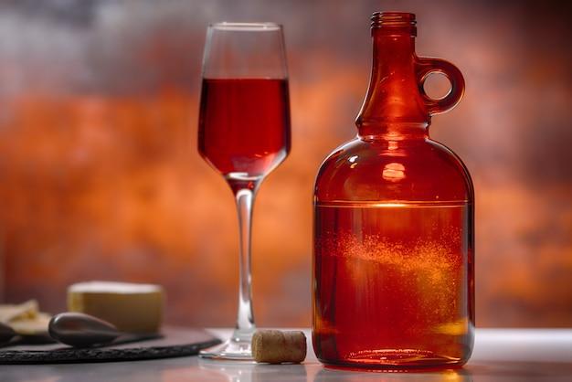 Copo de vinho tinto, decantador e tábua de queijos em um balcão de bar ou taverna