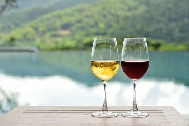 Copo de vinho tinto e branco gelado na mesa perto da piscina