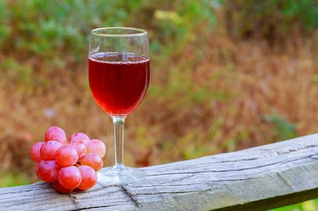 Copo de vinho tinto e cacho de uvas na mesa de madeira contra vinhedo no verão