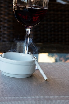 Copo de vinho tinto e cigarro em um cinzeiro branco sobre a mesa de um café de rua, verão na varanda de um restaurante, maus hábitos, alcoolismo e tabagismo