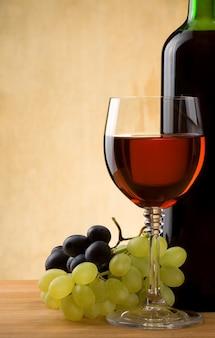Copo de vinho tinto e garrafa com uva na madeira