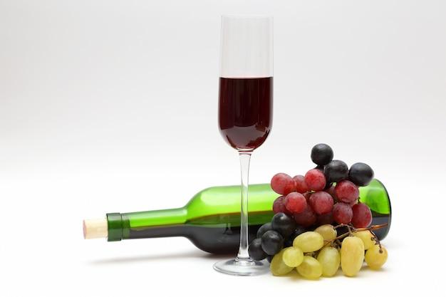 Copo de vinho tinto e garrafa com uvas em um branco