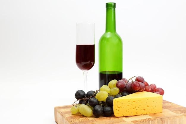 Copo de vinho tinto e garrafa com uvas