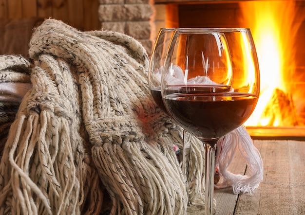 Copo de vinho tinto e lã coisas perto da lareira.