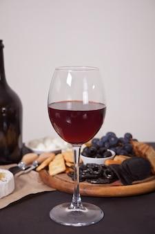 Copo de vinho tinto e prato com queijo variado, frutas e outros petiscos para festa