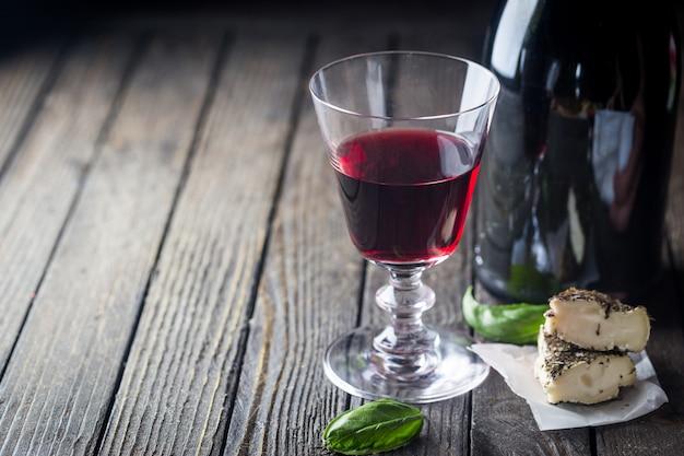 Copo de vinho tinto e uma garrafa em fundo escuro de madeira