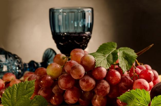 Copo de vinho tinto e uva rosa madura fresca num prato vintage, em uma parede de madeira velha.