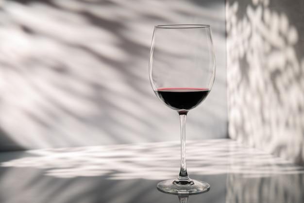 Copo de vinho tinto em um espaço de parede com belas luzes e sombras