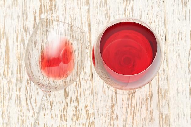 Copo de vinho tinto em uma mesa de madeira branca, vista superior.