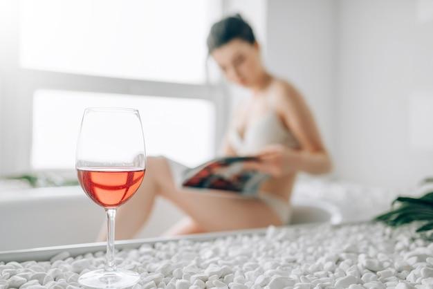Copo de vinho tinto, mulher atraente em cueca branca lendo revista no banho