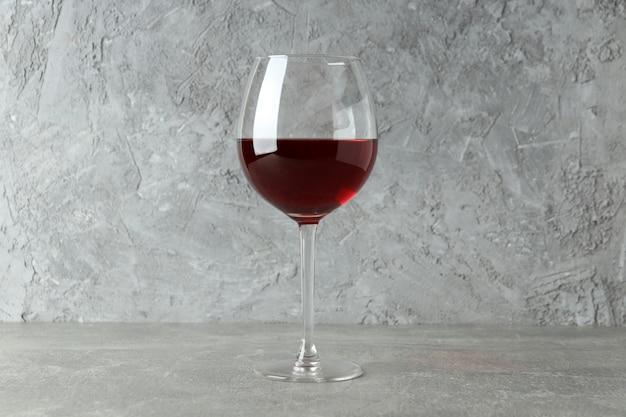 Copo de vinho tinto na mesa cinza texturizada