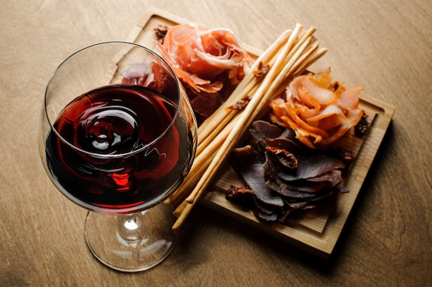 Copo de vinho tinto seco e vários tipos de carnes curadas em uma placa de madeira