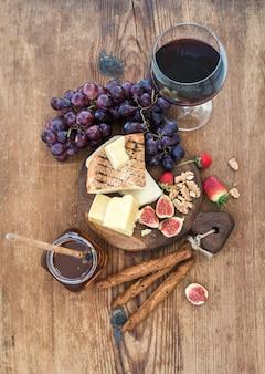 Copo de vinho tinto, tábua de queijos, uvas, figo, morangos, mel e pão gruda na mesa de madeira rústica