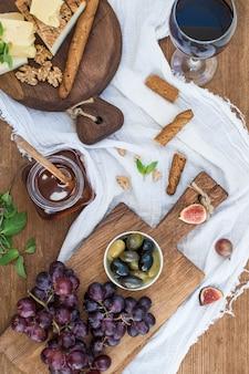 Copo de vinho tinto, tábua de queijos, uvas, nozes, azeitonas, mel e pão gruda na mesa de madeira rústica