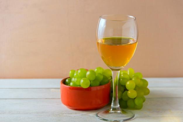 Copo de vinho, uvas verdes no prato na mesa.