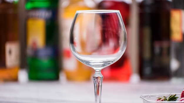Copo de vinho vazio e limpo. vidro no fundo desfocado. bem-vindo ao bar. beba o que quiser.