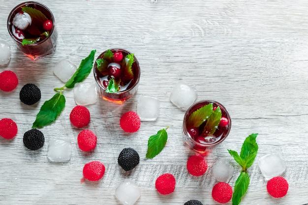 Copo de vinho vermelho tiro cocktail alcoólico frio com framboesas e hortelã
