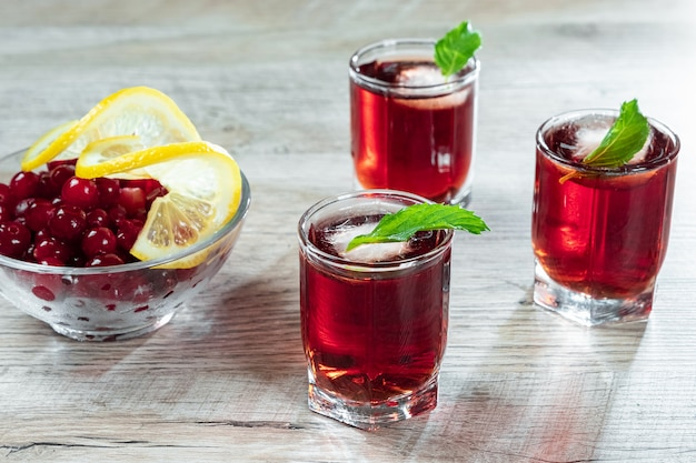 Copo de vinho vermelho tiro coquetel frio alcoólico com cranberries framboesas limão e hortelã