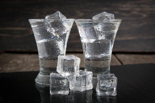 Copo de vodka com gelo na mesa de madeira.