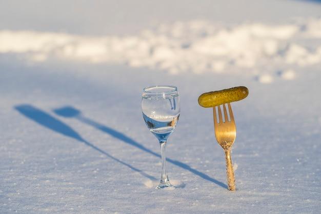 Copo de vodka e um garfo com pepino em conserva em uma neve branca no inverno, close up, ucrânia