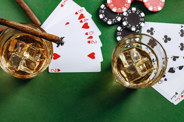 Copo de whisky charuto jogando cartas e fichas na superfície verde