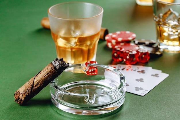 Copo de whisky charuto jogando cartas e fichas no fundo verde