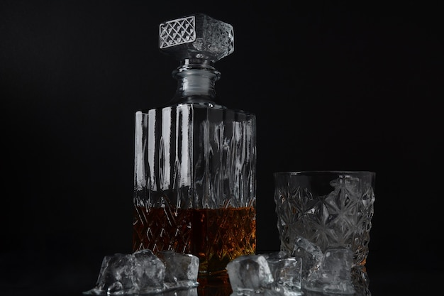 Copo de whisky com cubos de gelo e uma garrafa quadrada