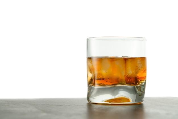 Copo de whisky com cubos de gelo em cima da mesa.