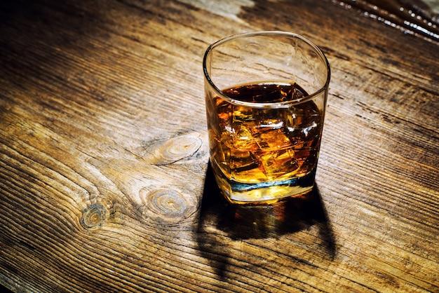 Copo de whisky com cubos de gelo na mesa de madeira