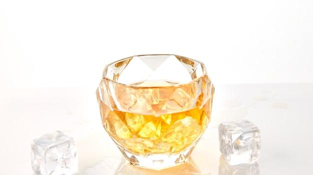 Copo de whisky com cubos de gelo no fundo branco com reflexão.