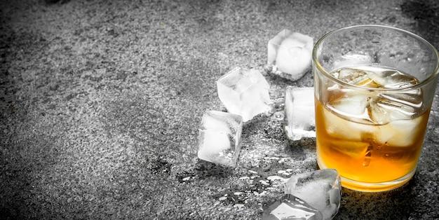 Copo de whisky com cubos de gelo. sobre um fundo rústico.