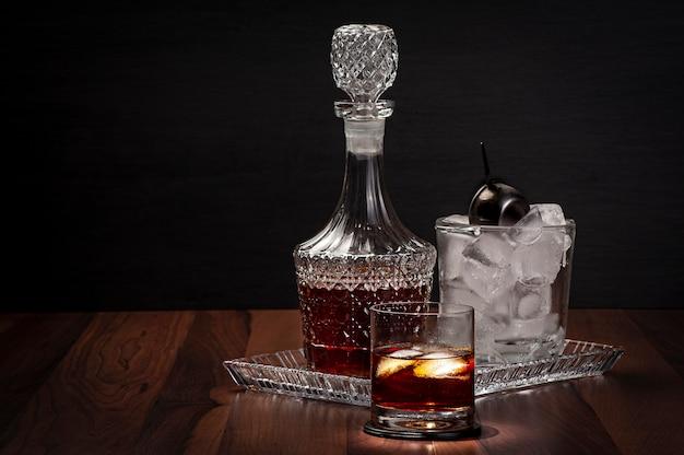 Copo de whisky com uma garrafa e um balde de gelo de vidro