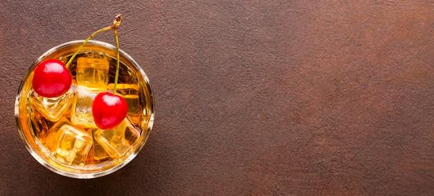 Copo de whisky com vista superior com cerejas e espaço de cópia
