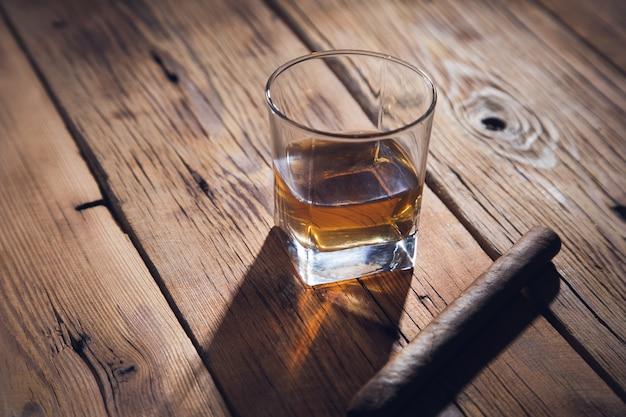 Copo de whisky e cigare no fundo de madeira