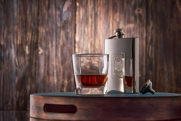Copo de whisky e um frasco na mesa de madeira