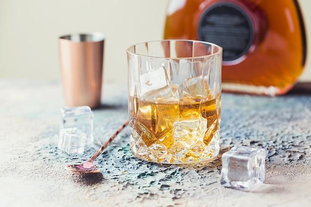 Copo de whisky escocês com cubos de gelo, garrafa e acessórios de barra de cobre
