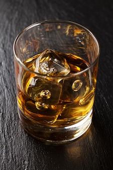 Copo de whisky escocês com gelo na mesa de pedra preta