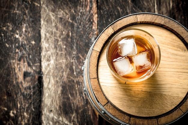 Copo de whisky escocês com um barril