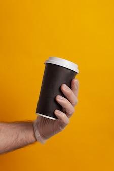 Copo descartável segurado por uma mão com luva de proteção
