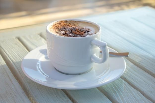Copo do cappuccino com arte do latte do cardamomo na tabela branca de madeira.