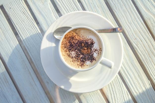 Copo do cappuccino com arte do latte na tabela branca de madeira. vista do topo.