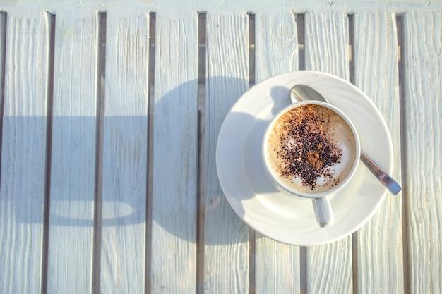 Copo do cappuccino com arte do latte no fundo branco de madeira. vista do topo.