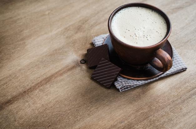 Copo do cappuccino com uma parte de chocolate.