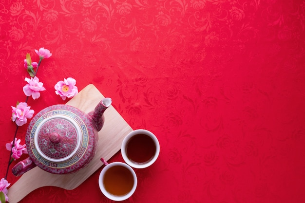 Copo do chá com espaço da cópia para o texto no fundo vermelho da textura, fundo chinês do ano novo.