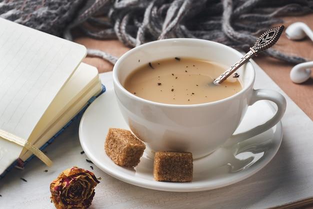 Copo do chá com leite, açúcar anis marrom e um bloco de notas. bandeja na colcha. tom vintage. conceito de estilo de vida.