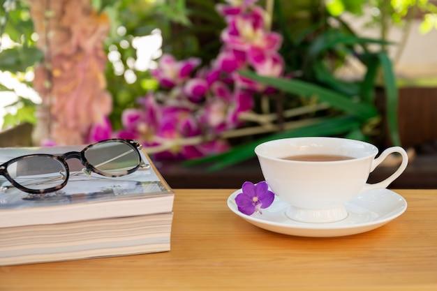 Copo do chá com livros e vidros dos olhos na tabela de madeira no jardim.