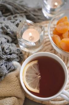 Copo do chá e abricós secados em uma tabela, em velas e em cobertor knited.