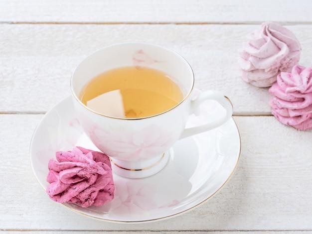 Copo do chá e marshmallow cor-de-rosa e chá verde no branco. comida. confeitaria e bebidas