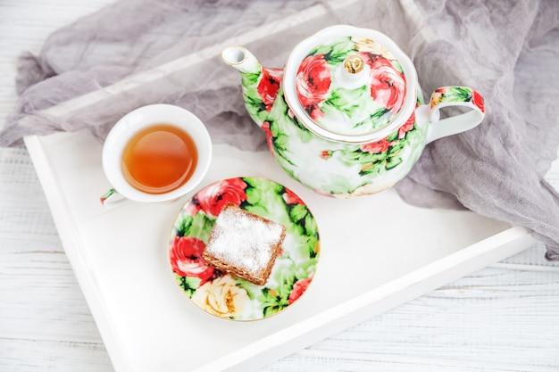 Copo do chá e pedaço de bolo em uma bandeja de madeira. festa de verão.