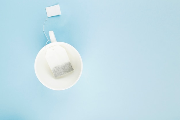Copo do chá e saquinhos de chá no fundo azul.
